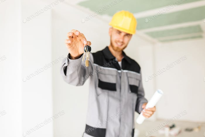 Close up photo of young engineer in work clothes and yellow hard