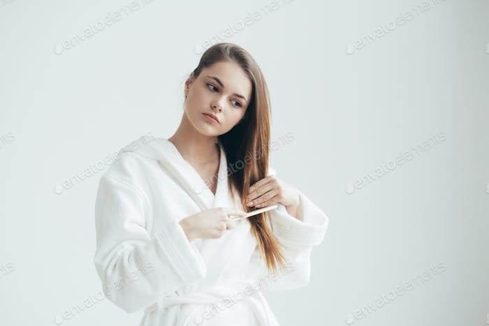Woman in bath robe over white background, beautiful female blonde hair beauty concept. Studio shot.