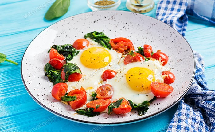 Plate with a keto diet food. Fried egg, spinach, and tomatoes. Keto, paleo breakfast.