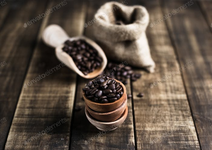 coffee beans with wooden saucer scoop and bag