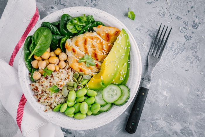 Buddha bowl with spinach, quinoa, chickpeas, grilled chicken, avocado, edamame beans, cucumbers