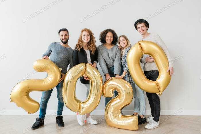 Group of cheerful intercultural young friends holding inflatable numbers
