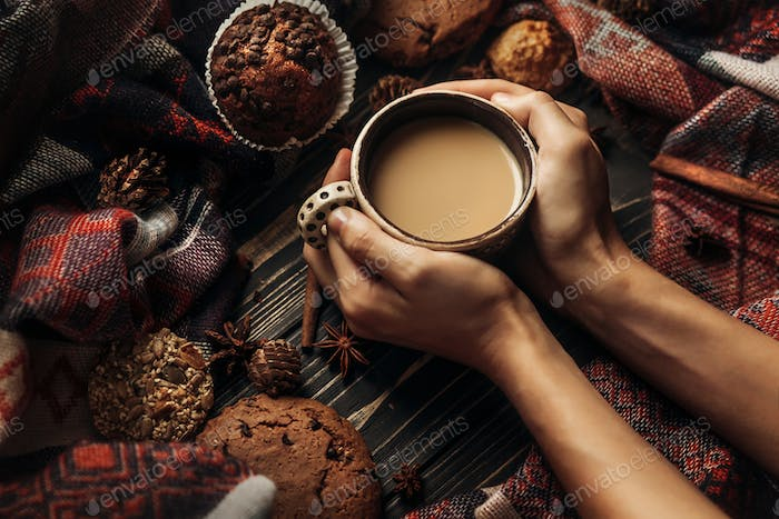 Hands holding coffee cookies and spices on wooden background