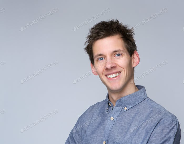 Smiling young man posing against gray background