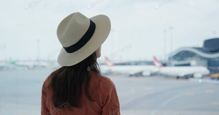 Woman look at the window outside in the airport