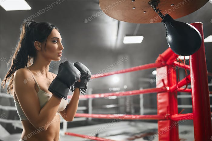 Female boxer hitting small punching bag