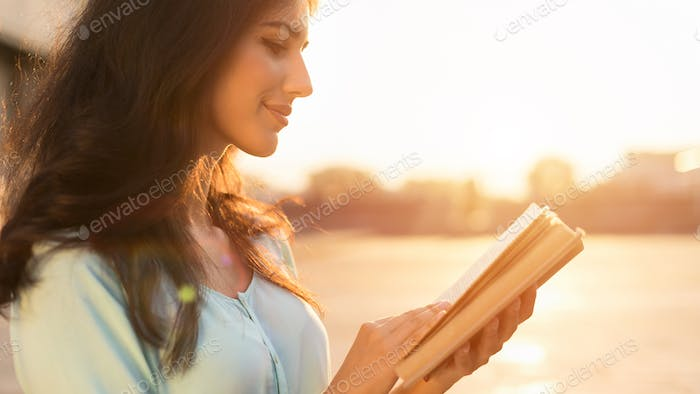 Reading book outdoors. Young woman walking in city at sunset