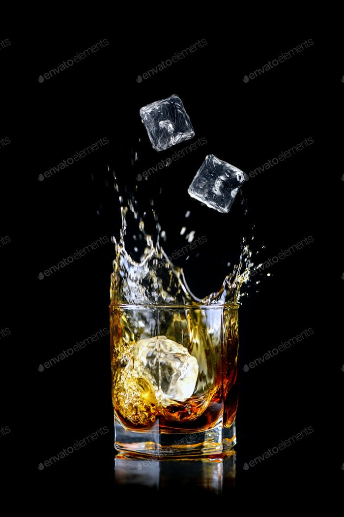 Splashing of whiskey out of glass isolated on black