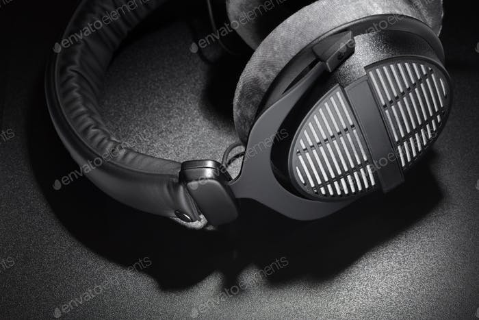 Black studio headphones on dark background