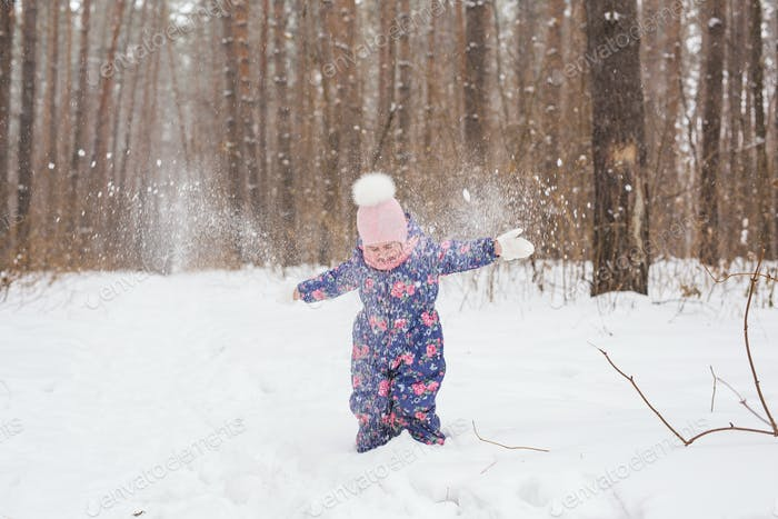 Childhood and nature concept - Adorable child playing in winter park