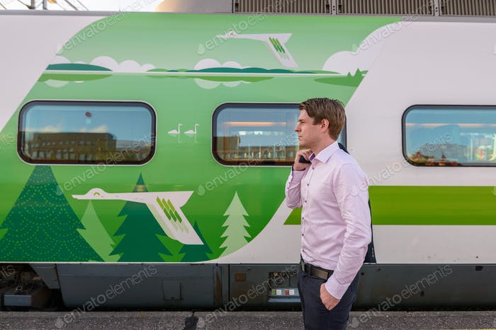 Profile view of young handsome businessman in front of train at railway station