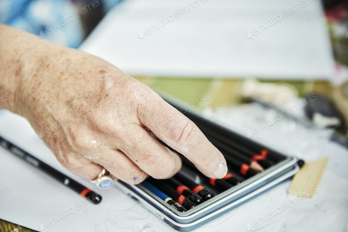 An artist selecting a pencil from a box.