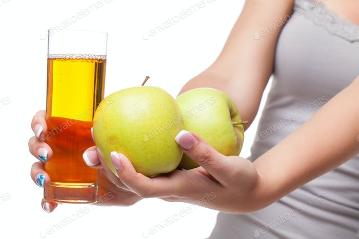 Beautiful girl hands with apple and glass of juice