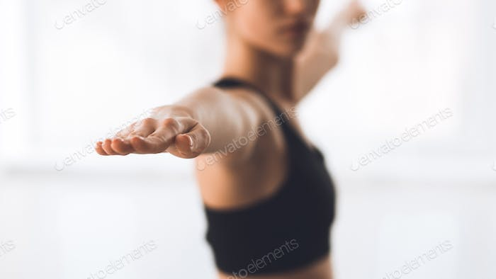 Woman exercising yoga in warrior pose, focus on hand