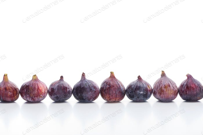 Ripe Whole Delicious Figs in Row on White Background
