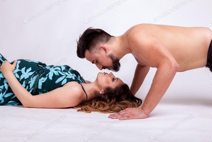 Pregnant woman lying and husband kising her
