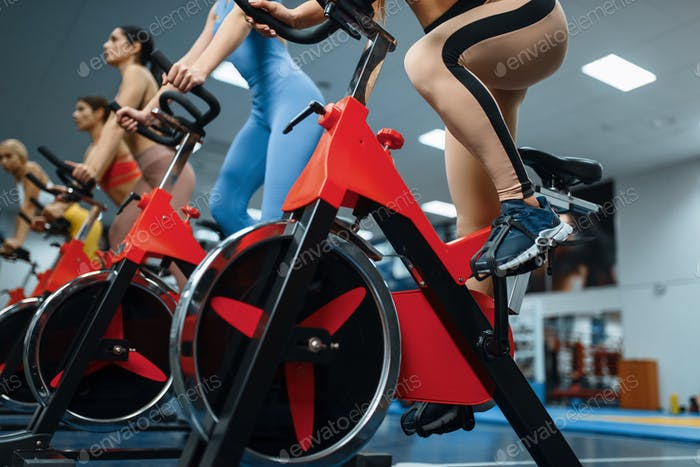 Женщины на стационарных велосипедах в тренажерном зале, вид снизу
