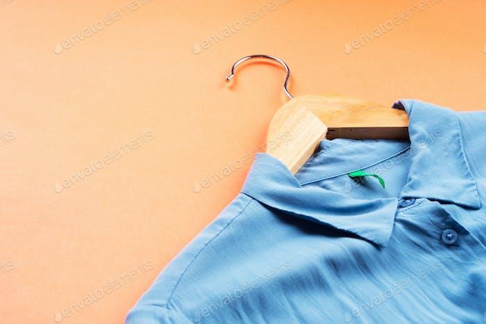 Blaues Frauenhemd auf Aufhänger auf orange