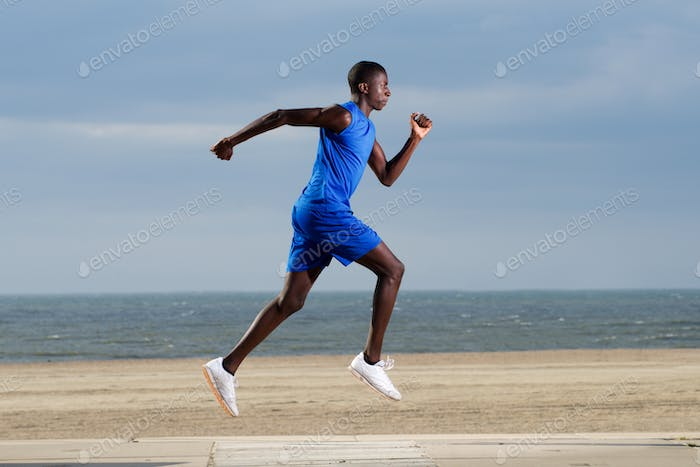 Fit young african man running along the beach