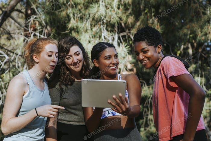 Group of active women looking at a digital tablet
