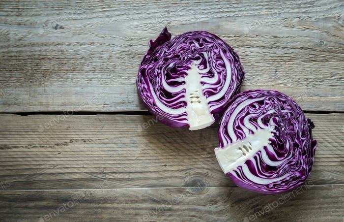 Two halves of red cabbage on the wooden background