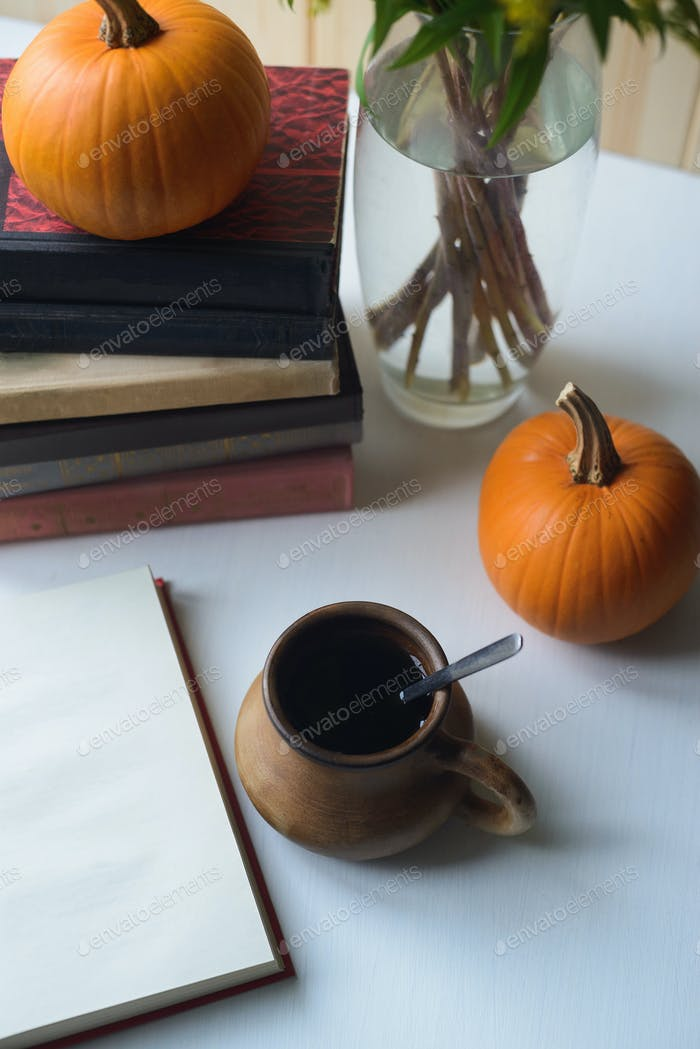 autumn still life with books, pumpkins, cup