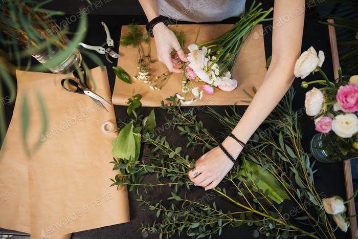 Hands of woman florist creating flower bouquet on table