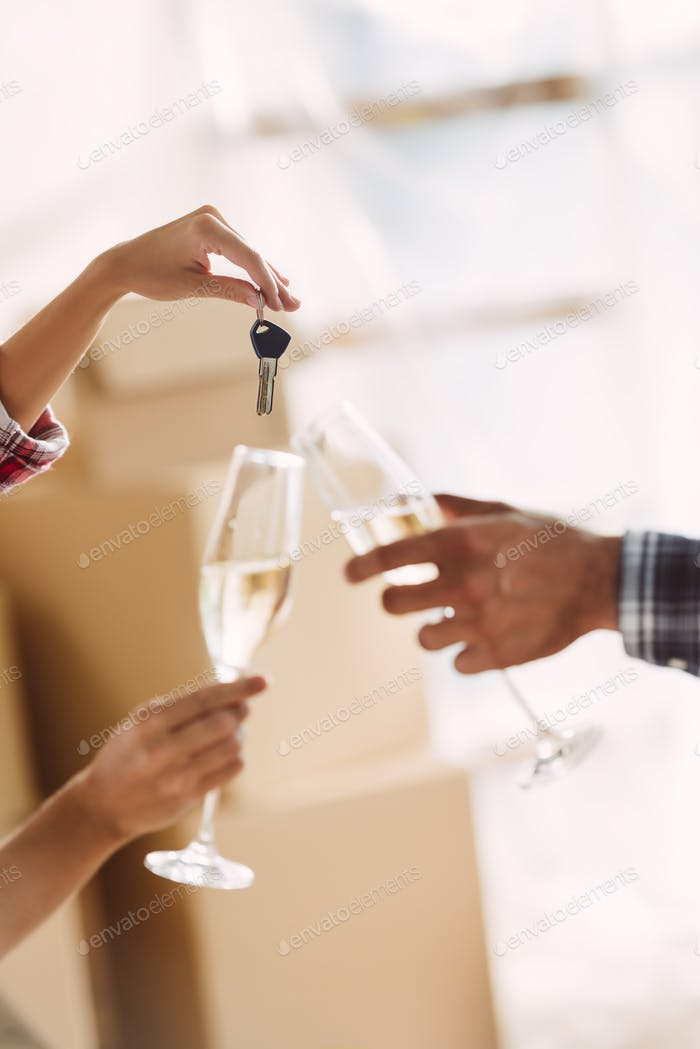close-up partial view of couple holding glasses of champagne and keys from new house