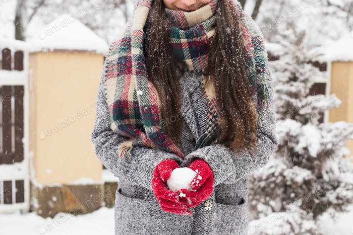 Girl wearing red covered gloves holding snow with Merry Christmas greeting