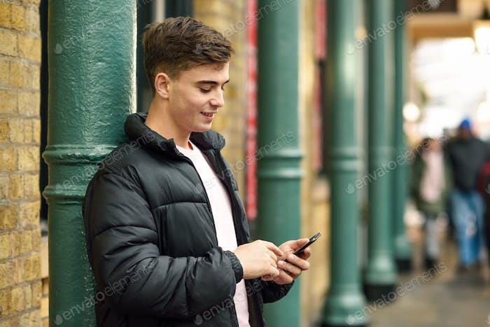 Молодой городской человек использует смартфон в городском фоновом режиме.