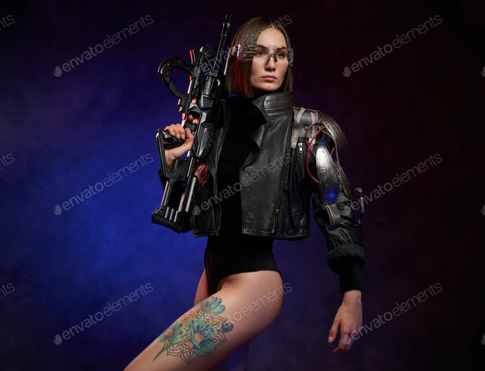 Futuristic cyber woman holding rifle in dark and atmospheric studio