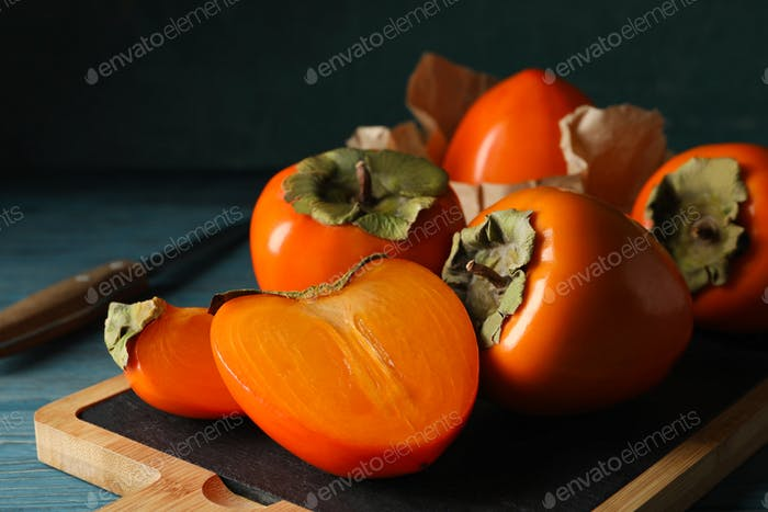 Board with ripe persimmon and knife on wooden background