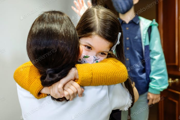 Mother hugging daughter with mask coming back from school