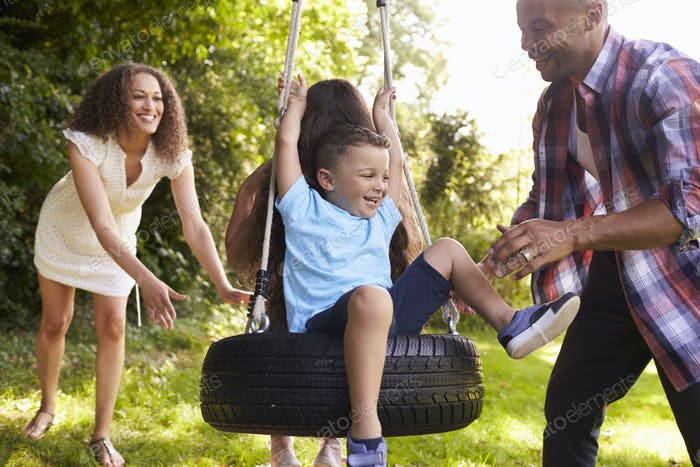 Parents Pushing Children On Tire Swing In Garden
