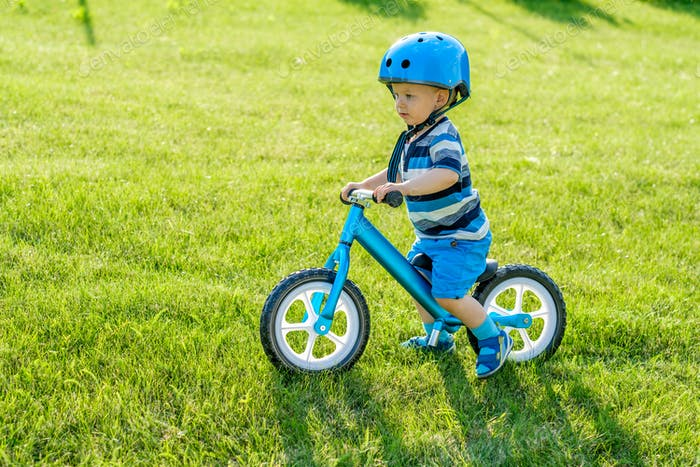 Boy in helmet riding a blue balance bike (run bike)