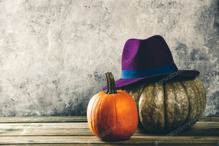 Autumn background with pumpkins and purple felt hat