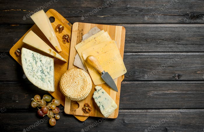 Assortment of different cheeses with grapes and walnuts.
