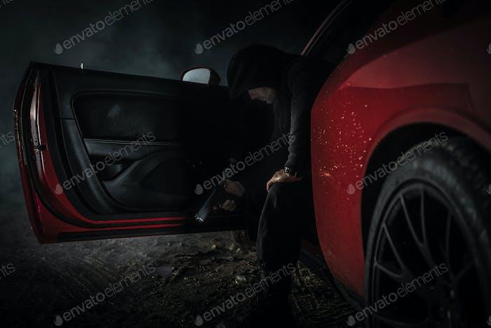 Nachdenklicher kaukasischer Gangster mit Pistole in seinem Auto