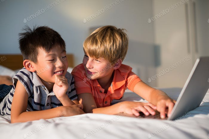 Smiling siblings using laptop on bed