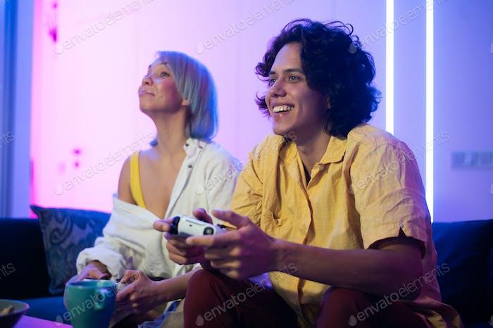 Foto eines jungen Paares, das nachts zu Hause Video spiele spielt