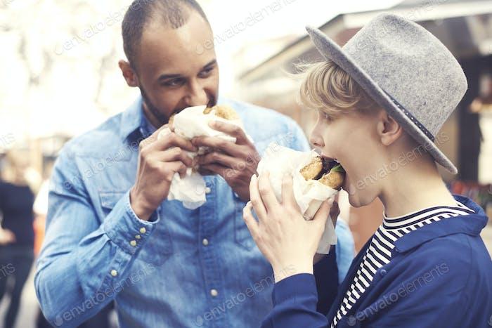 Couple having delicious burgers outside