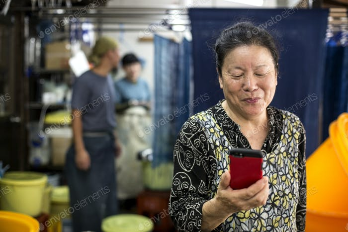 Smiling Japanese woman standing in a textile plant dye workshop, using her mobile phone.