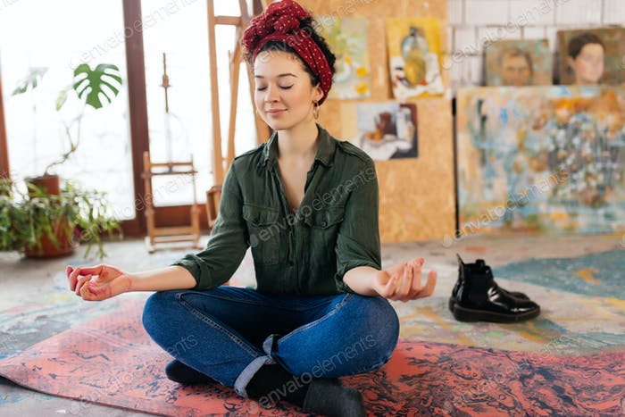 Young pretty woman with closing eyes sitting on yoga mat in lotu