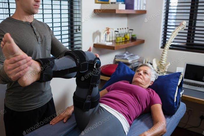Male physiotherapist giving leg massage to patient