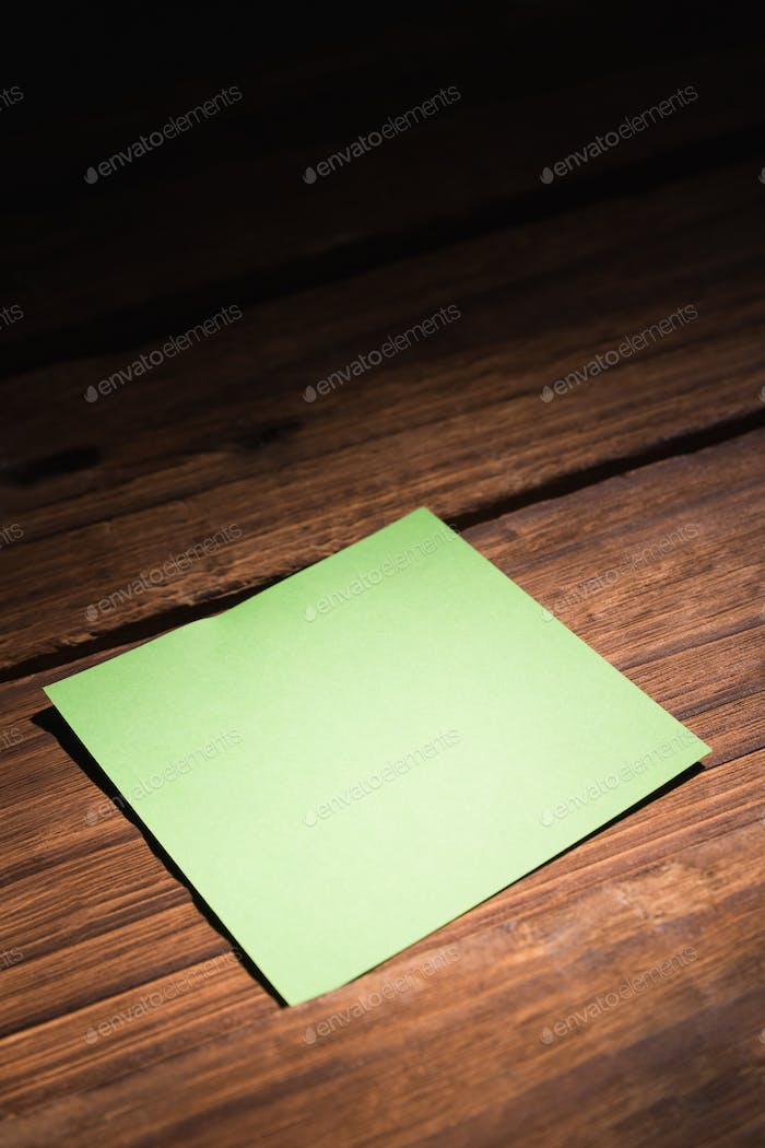Green post it on wooden background