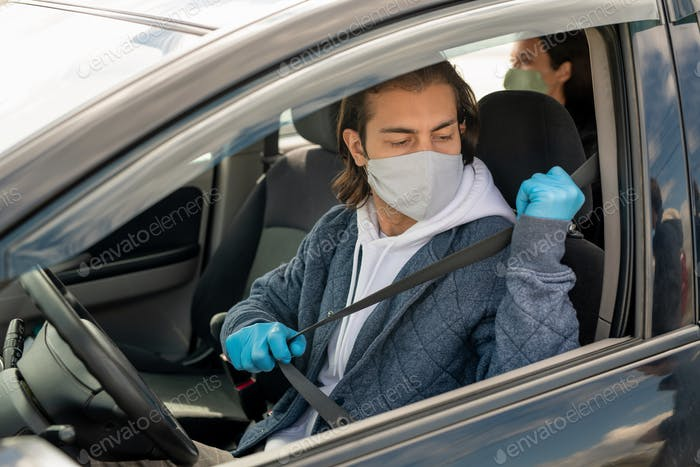Young man in gloves and mask going to put seatbelt while sitting in car