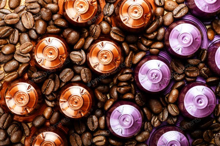 Espresso coffee capsules or pods and coffee beans on wooden rustic background