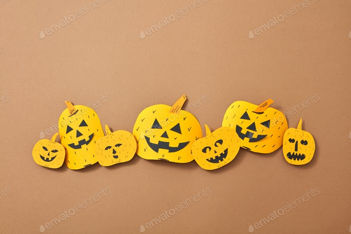 Pattern of paper handcraft pumpkins with scary faces on a brown background with copy space