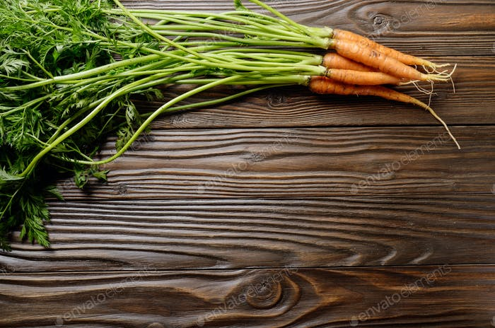 Top view at Fresh organic carrots on kitchen wooden rustic table