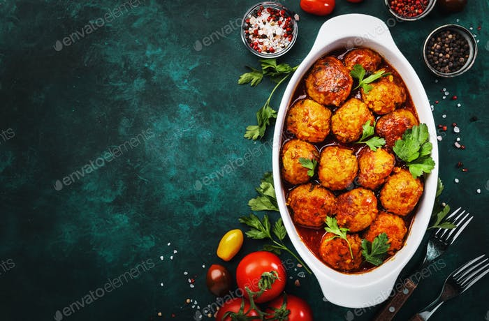 Meatballs with tomato sauce and spices in baking dish